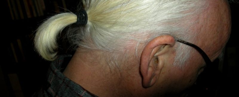 Man's white-haired ponytail on a black background.